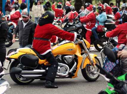 person in santa suit riding yellow cruiser motorcycle